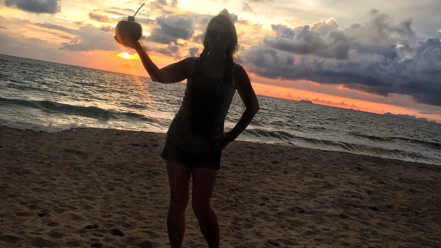 Silhouette in sunset with coconut